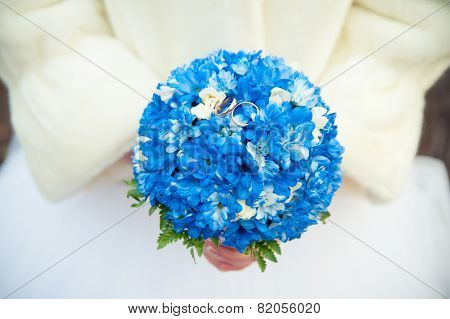Bride In A Fur Coat Holding A Bouquet Which Lie Wedding Rings