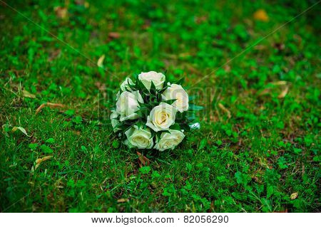 Bridal Bouquet Of White Roses Lying On The Grass