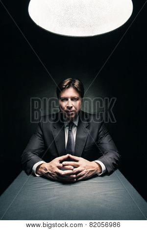 Man wearing suit in dark room illuminated by lamp