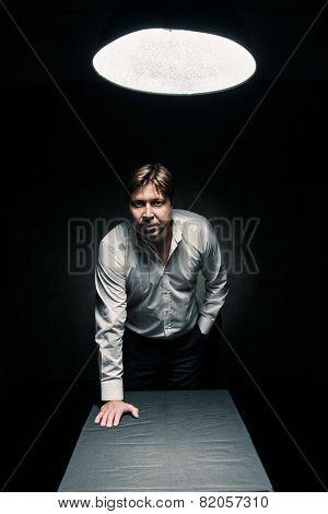 Man in dark room illuminated by lamp