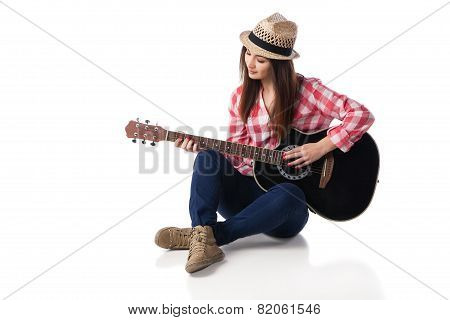 woman musician playing guitar sitting on floor.
