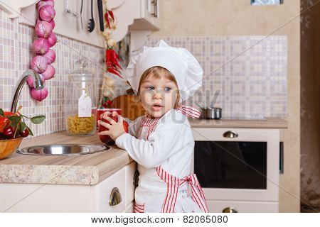Little Girl In Apron In The Kitchen. .