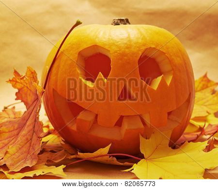 Pumpkin Jack-o'-lantern over maple-leaf