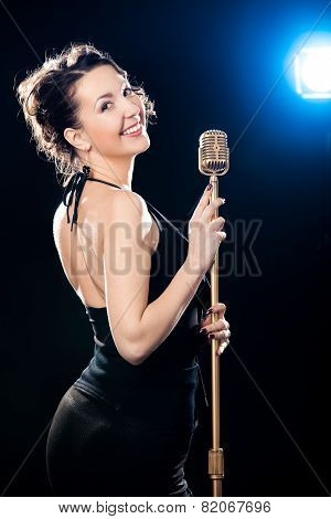 Cheerful Beautiful Young Woman Singer Holding Golden Vintage Microphone Lit By Projector