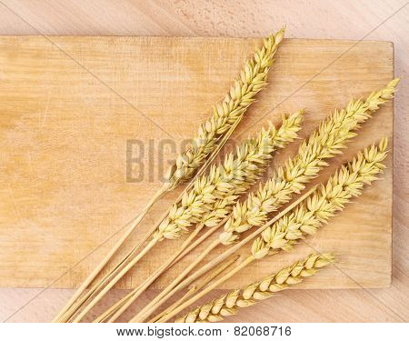 Ears of wheat over the cutting board