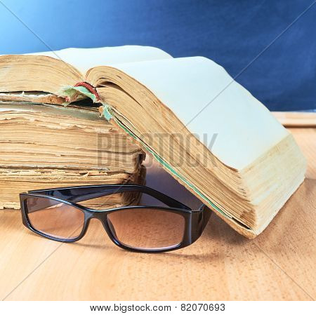 Glasses, old books and blackboard composition