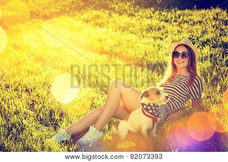 Hipster Girl with her Dog Lying on the Grass