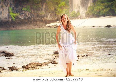 Young Blonde Bride Walks Barefoot On Sandy Beach