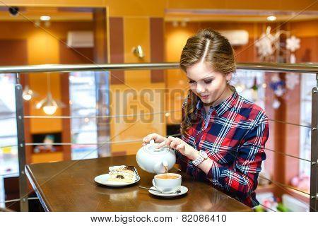 Young Women In A Plaid Shirt Pours Green Tea