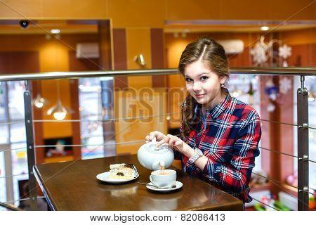 Beautiful Girl In A Plaid Shirt Pours Green Tea