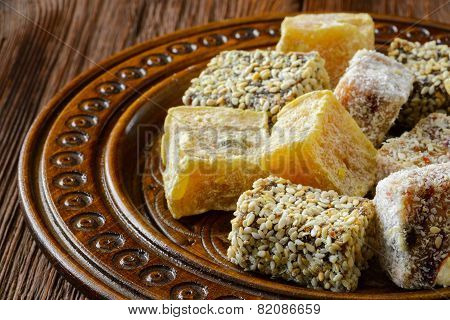 Turkish delight or rahat lokum on wooden plate. Selective focus