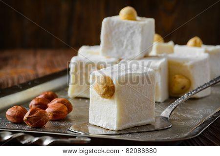 Turkish delight. Eastern dessert with hazelnut on metal plate. Selective focus