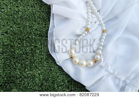 Plastic Perl Necklace On White Fabric