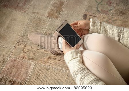 Female With Smartphone On Vintage Carpet