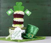 pic of leprechaun hat  - Happy St Patricks Day triple layer cupcake with shamrock decorations and leprechaun hat against a vintage style green wood background - JPG