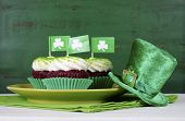 pic of cupcakes  - Happy St Patricks Day cupcakes with green theme decorations on vintage style green wood background.