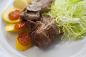 picture of veal  - Veal carrots mushrooms zucchini and salad on a plate - JPG