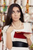 stock photo of holding money  - Portrait of a funny girl looking for money in her purse - JPG