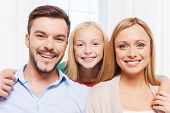 stock photo of family bonding  - Happy family of three bonding to each other and smiling while sitting indoors - JPG