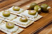 image of brie cheese  - close up of slices of brie cheese on everything crackers with sliced olives on top - JPG