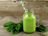 image of greens  - Healthy green smoothie with spinach in a jar mug against a wood background - JPG
