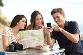 picture of generic  - Group of young tourist friends consulting gps map in a smart phone in a restaurant with the beach in the background - JPG