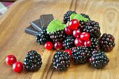 image of blackberries  - Fresh juicy blackberries and cranberries with chocolate and mint on wooden dish - JPG