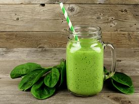 stock photo of smoothies  - Healthy green smoothie with spinach in a jar mug against a wood background - JPG