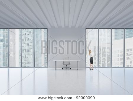 Side View Of The Blonde Employee Who Looks Out The Window In New York's Panoramic Office. A Concept