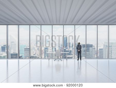 Rear View Of The Businessman Who Looks Out The Window In New York's Panoramic Office. A Concept Of T