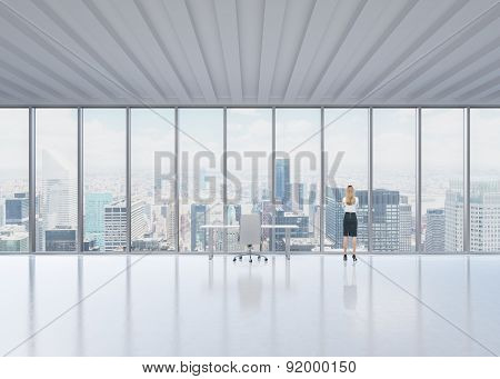 Rear View Of The Blonde Employee Who Looks Out The Window In New York's Panoramic Office. A Concept