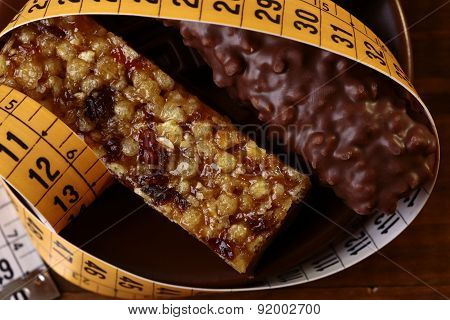 Tasty Chocolate Bars And Peanut Brittle With A Measuring Tape