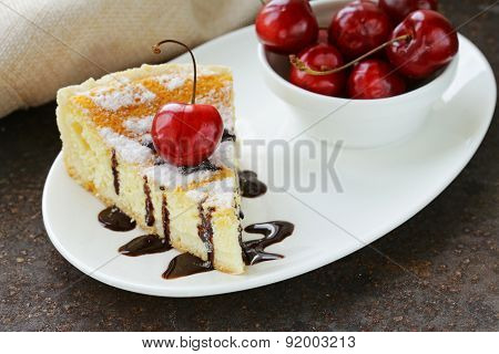 homemade cheesecake with powdered sugar and cherry on a white plate