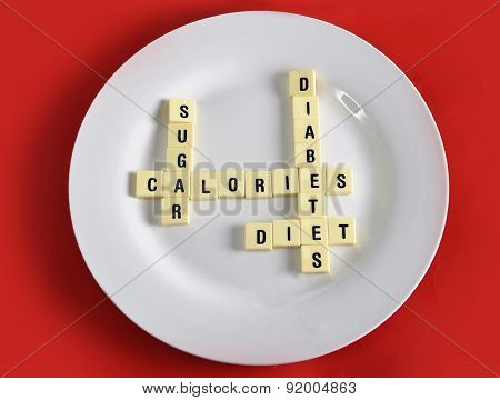 Crossword Game On Dish On Table Red Mat With Words Sugar , Calories, Diabetes And Diet Taking In Sug