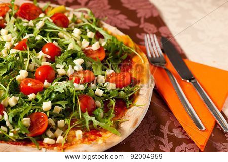 Pizza With Rucola And Cherry Tomatoes On A Teble Of Italian Restaurant