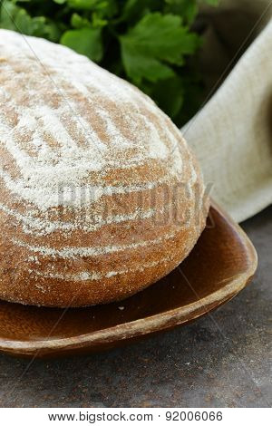 homemade loaf of rye bread on a wooden plate