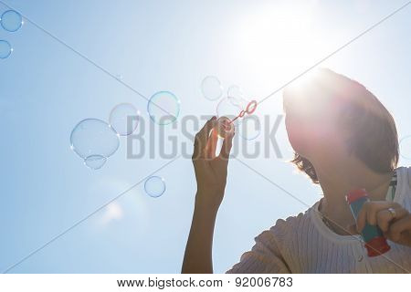 Young Woman Joyfully Blowing A Stream Of Soap Bubbles.