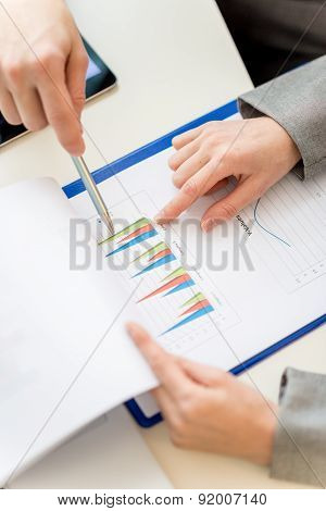 Businesspeople Pointing At The Graph On Document