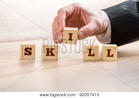 Businessman Arranging Blocks To Form Skill Word
