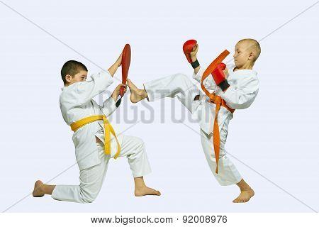 Boys are training kick leg on simulator