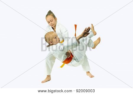 In judogi the little sportswoman is training throw