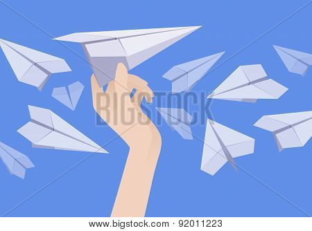 White paper airplane in the female hand and other planes nearby