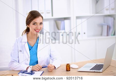 Female doctor sitting on the desk and working a laptop.