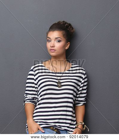 A young woman standing, isolated on gray background