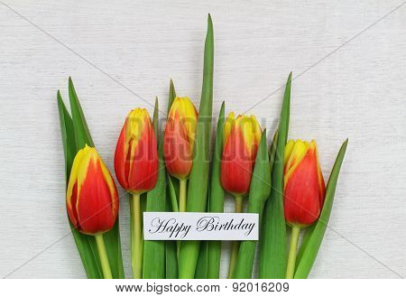 Happy birthday card with red and yellow tulips on white wooden surface