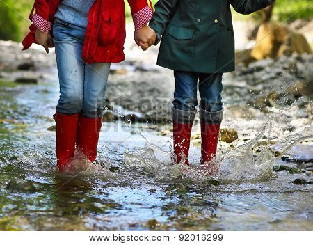 Child Wearing Rain Boots Jumping. Close Up