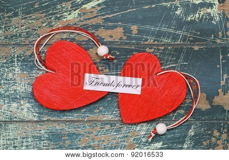 Friends forever card with two red wooden hearts on rustic wood