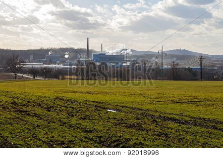 Factory, green field and cloudy sky