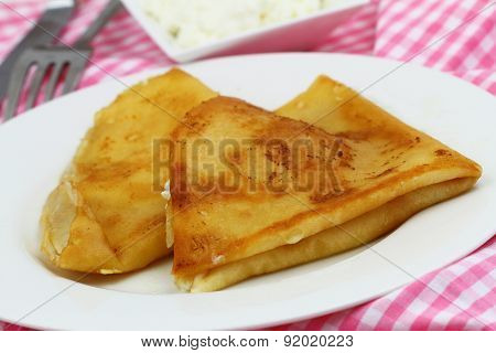 Crepes with cottage cheese on white plate