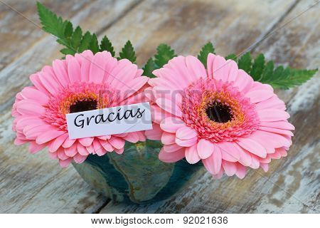 Gracias (which means thank you in Spanish) with pink gerbera daisies